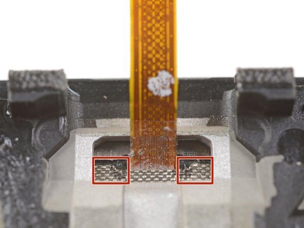Insert the point of a spudger into the marked areas on either side of the flex cable, and push until the fingerprint scanner is loosened from its recess.