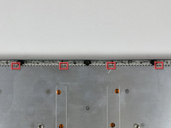 Use the tip of a spudger to bend each of the four keyboard lock tabs away from the underside of the keyboard enclosure on the lower case.
