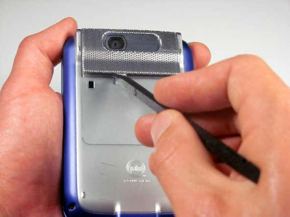 Use either end of the spudger to carefully pry off the camera lens mesh cover.