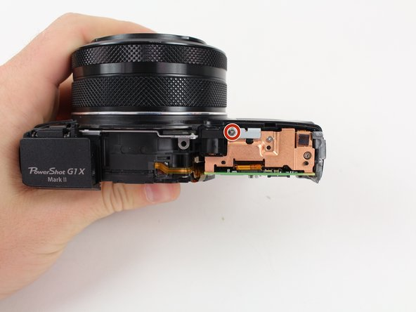 Remove the 3.5mm Phillips screw from the grey tab on the top of the camera with a Philips Head screwdriver.