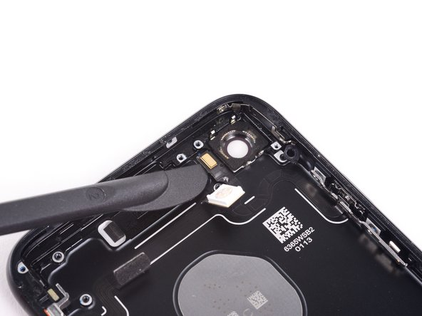 Use the blade of a Halberd spudger to separate the adhesive holding the microphone to the rear case.