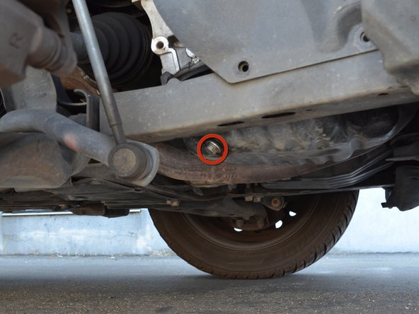 Locate the oil drain plug at the back passenger side corner of the oil pan and place an oil drain pan underneath it.
