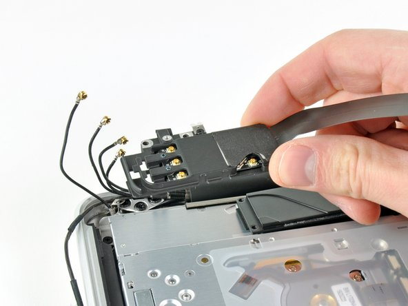 Remove the AirPort/Bluetooth assembly, minding the fragile antenna contact near the corner of the upper case.