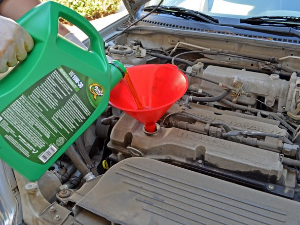 Pour 4 quarts of 10W-30 oil into the engine. Use one hand to stabilize the funnel to help prevent spills.
