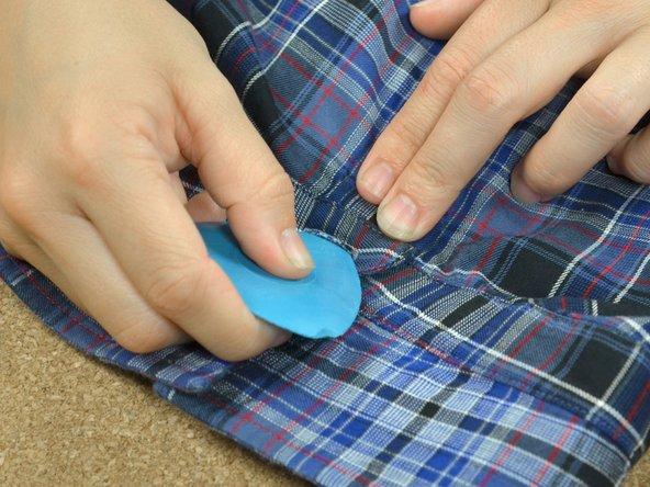 Das Knopfloch über die Stelle legen, an der der Knopf sitzen sollte. Durch das Knopfloch hindurch die Stelle mit Schneiderkreide markieren.