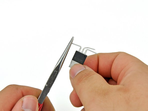 Use needle nose pliers to bend just the tips (approximately 2 mm) of the pins 90° up so that they are pointing the same direction as the IC face.