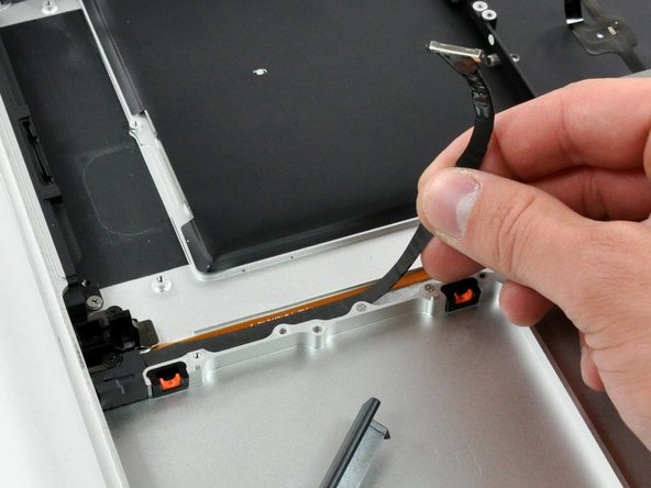 Peel the hard drive cable from the adhesive securing it to the upper case, and maneuver the plastic retaining block out of the upper case.