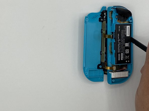 Insert a spudger between the battery and the Joy-Con housing.