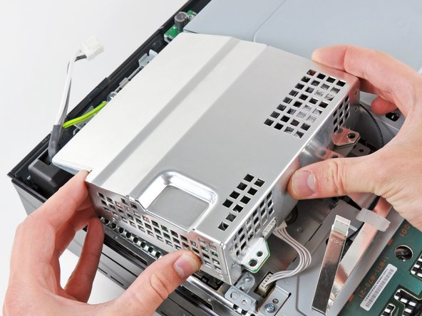 Lift the power supply upward from its front edge to disconnect it from the posts attached to the logic board.