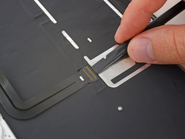 Use a spudger to flip up the retaining flap on the keyboard ribbon cable ZIF connector.