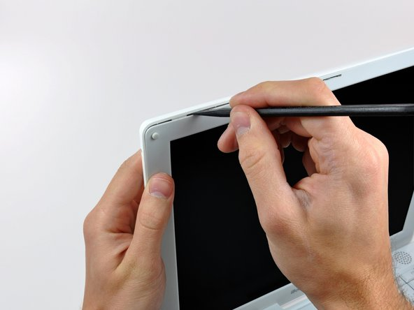 Insert the flat end of a spudger perpendicular to the face of the display into the gap between the front and rear bezels near the upper left corner of the display.