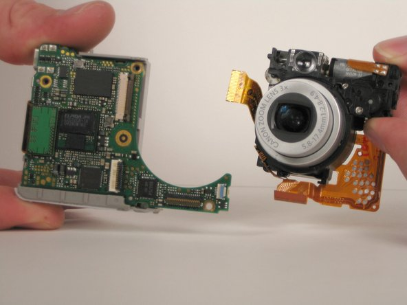 Pull the lens assembly away from the motherboard assembly.