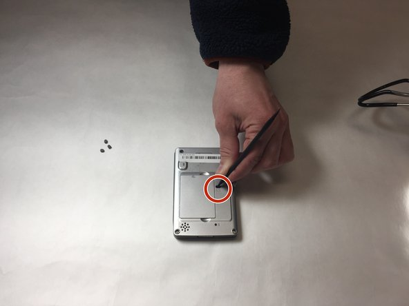 Insert the nylon spudger into the battery cover release slot to remove the battery from the device.