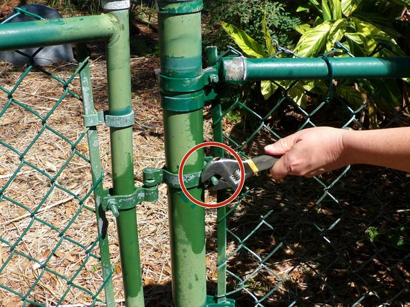 Remove the bolt from the hinge strap on the fence post.