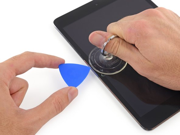 While holding the glass up with the suction cup, slide the point of an opening pick into the gap between the glass and body of the iPad.