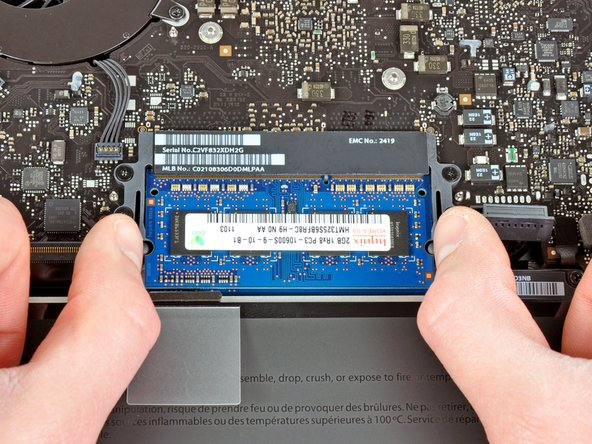 Pull the two RAM retaining arms away from the center of the RAM chip.