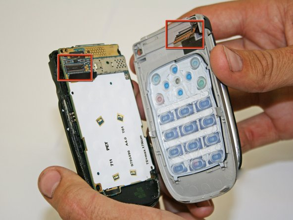 Gently pull the phone apart and the flexible wire should detach from its connection as shown.
