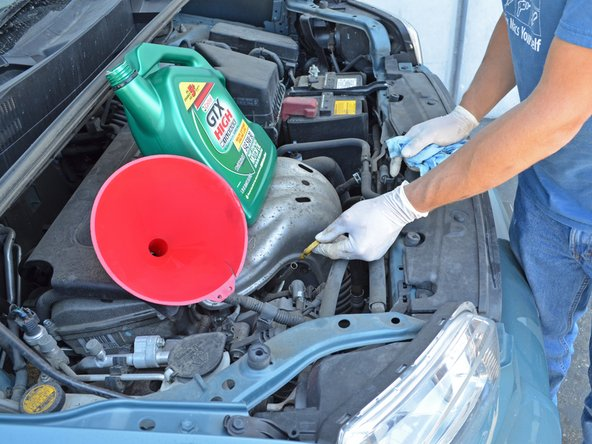 Grab the yellow handle of the engine oil dipstick at the front of the engine and pull the dipstick out.