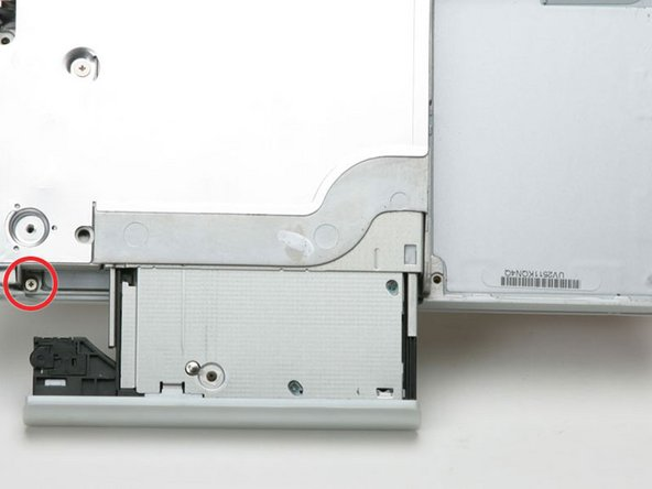 Pull the optical drive a bit more so that you can access and remove a second Phillips screw near the power receptacle.