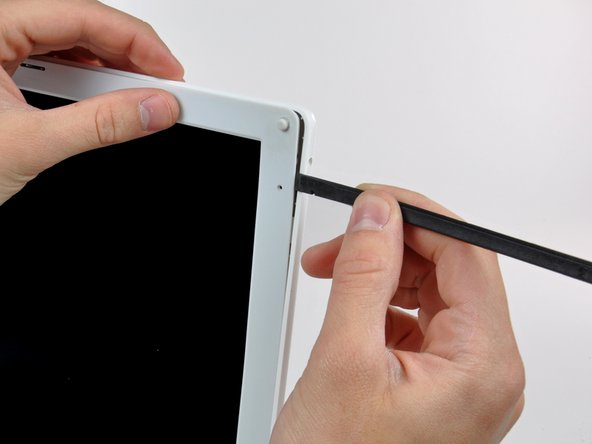 Use the flat end of a spudger to pry the rear bezel away from the right edge of the display.