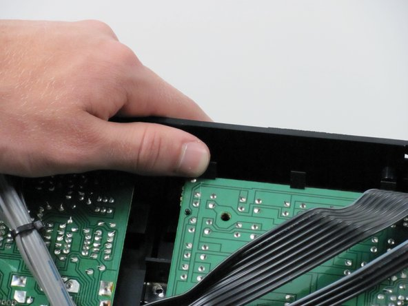 You will see the same snaps along the top of the logic board. Press the heads of the snaps down and pull the logic board out and up.