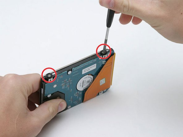 Remove the two Phillips screws and black rubber bumpers from the right side of the hard drive bracket.
