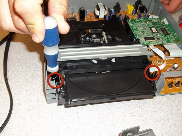 Using your philips screwdriver, remove the two screws at the base of the disc drive. (See image)