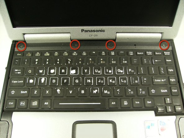 Open the laptop and remove the four indicated screws with a Phillips size 0 screwdriver.