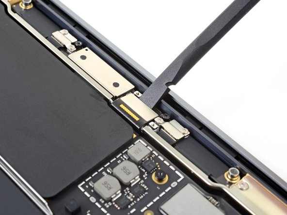Use the flat end of a spudger to pry the display cable connector straight off of the antenna board to disconnect it.