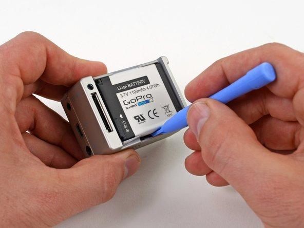 プラスチックの開口ツールをバッテリーとリアケースの間に差し込みスライドしてください。
