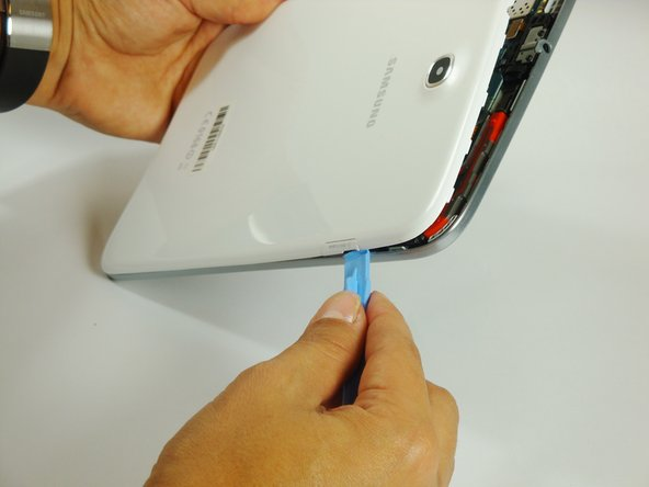 Work your way around the entire device by carefully prying and sliding the plastic opening tool.