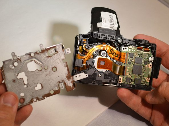 Using the spudger, remove the metal housing (Metal housing is removed from camera).