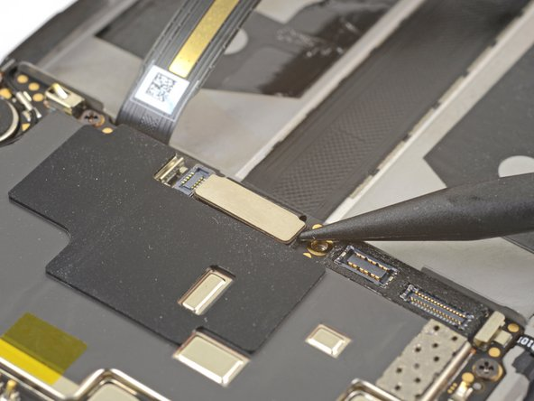 Use the point of a spudger to pry up and disconnect the display interconnect cable from its socket near the bottom edge of the motherboard.