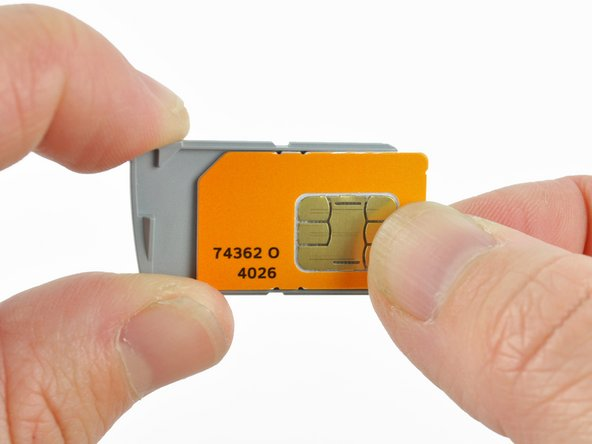 Remove the orange SIM card from the gray tray.