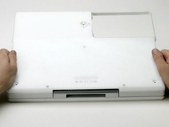Once the front and sides of the lower case are free, turn the computer so that the back is facing you.
