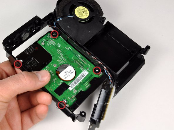 Hold the new drive in place and attach it to the frame using the four Phillips screws.