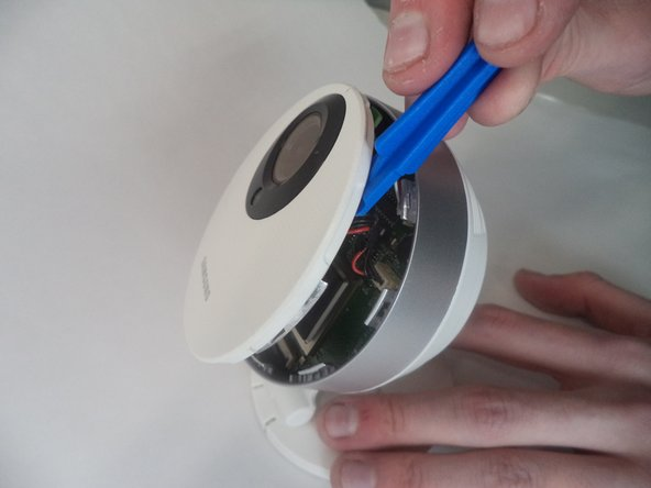 À l'aide d'un outil d'ouverture en plastique, appliquez une pression sur divers points autour de la caméra pour faire levier pour ouvrir le panneau avant.