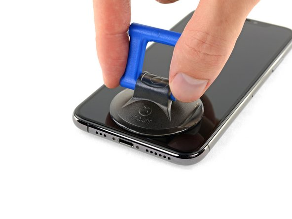 If you're using a single suction handle, apply it to the bottom edge of the phone, while avoiding the curved portion of the glass.