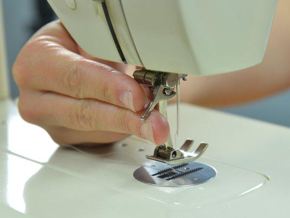Portare l'ago della macchina da cucire in posizione alzata ruotando il volantino verso se stessi.