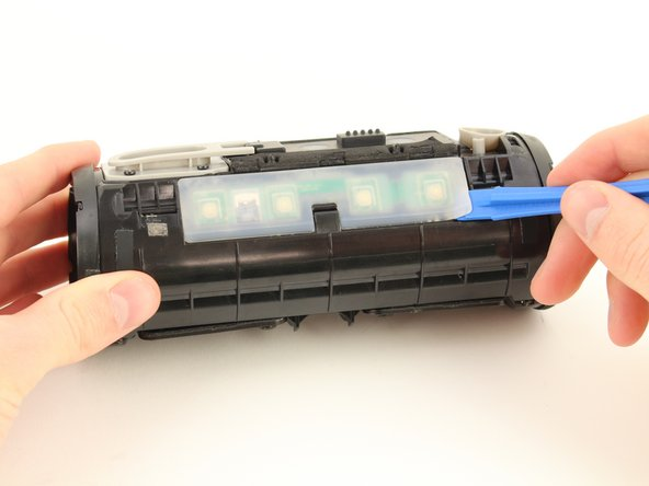 Insert the plastic opening tool under the clear rubber cover over the button control board.