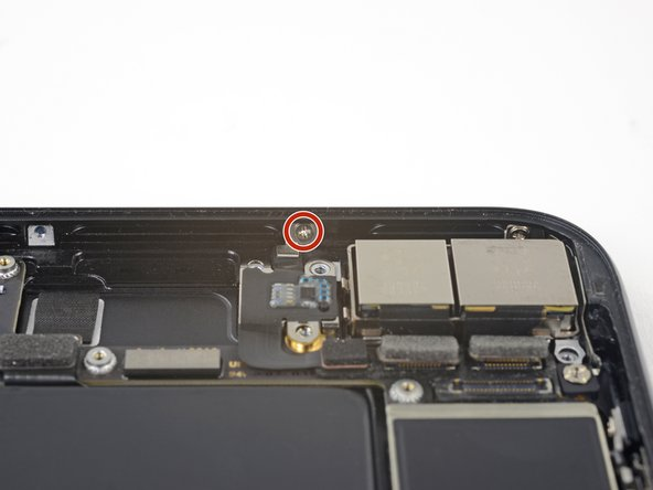 Remove the 1.3 mm Phillips screw securing the antenna flex cable to the top edge of the iPhone's rear case.