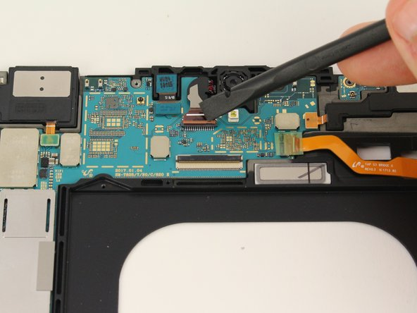 Remove the ribbon cable for the front facing camera after popping the red ZIF connector bar up with a spudger.
