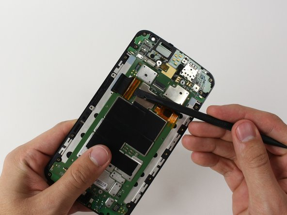 With a spudger, unlatch the ZIF connector of the big ribbon cable on the side of the phone. See instructions for detatching ZIF connectors here.