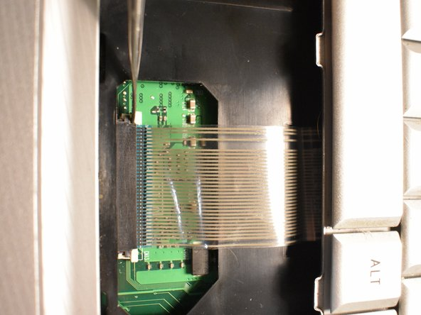 Gently disconnect the connector strip by pushing the white clips forward.